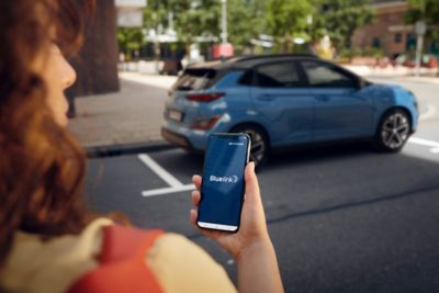 Woman using the Bluelink® app while walking towards her new Hyundai Kona Electric.