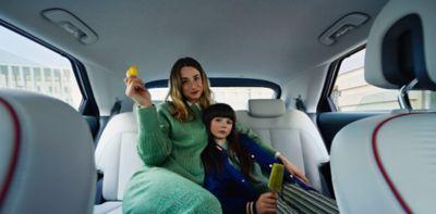Una madre y su hija sentadas en los cómodos asientos traseros del Hyundai IONIQ 5.