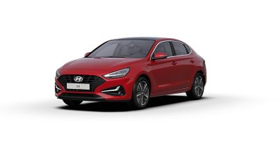 Front side view of the new Hyundai i30 Fastback in the colourSunset Red.