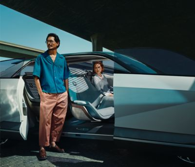 A man picture in front of the open door of a Hyundai electric vehicle concept.