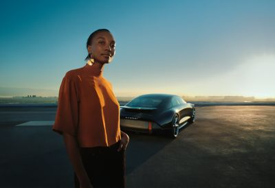 A woman standing in front of a Hyundai electric concept car.