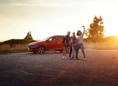 Photo showing a group a friends posing in front of the all-new Hyundai Kona.