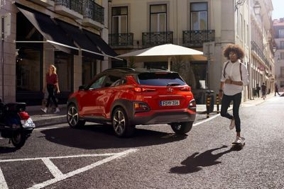 Photo of the all-new Hyundai Kona parking on a busy street.
