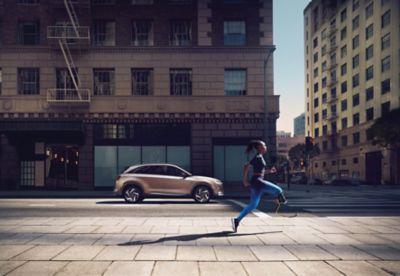 Kobieta biegnąca przed smaochodem Hyundai