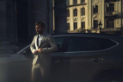Mężczyzna w garniturze opierający się o Hyundaia Tucson