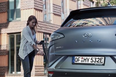 Vrouw tankt brandstofcel van Hyundai NEXO.