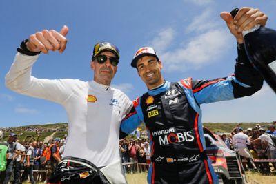 Kierowca Hyundai Motorsport Dani Sardo trzymający w ręku szampana i jego pilot Carlos del Barrio unoszący kciuk w górę, świętując zwycięstwo