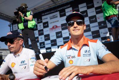 Kierowca Hyundai Motorsport Dani Sardo i pilot Carlos del Barrio ubrani w okulary przeciwsłoneczne podpisują autografy