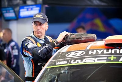 Hyundai Motorsport co-driver Carlos del Barrio holding a bag on the roof of the car