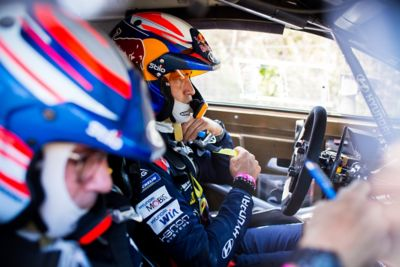 Hyundai Motorsport driver Dani Sardo fixing his helmet strap