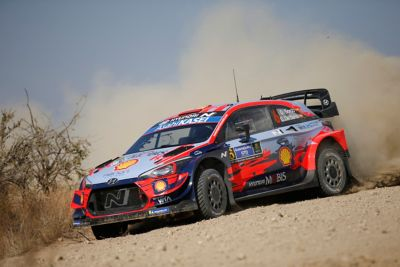 Hyundai i20 Coupe WRC with clouds of dust next to a bush