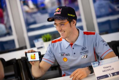 Hyundai Motorsport driver Thierry Neuville smiling showing an emoji on his phone screen