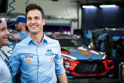 Hyundai Motorsport driver Dani Sardo smiling next to a crew member