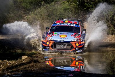 Hyundai i20 Coupe WRC driving through a mass of water spraying both sides