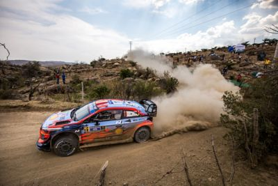 Hyundai Motorsport i20 Coupe WRC drifting around a bend leaving clouds of dust behind