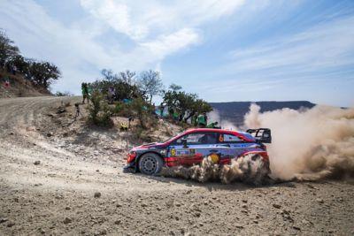 i20 Coupe WRC skręcający ostro w lewo w chmurze pyłu