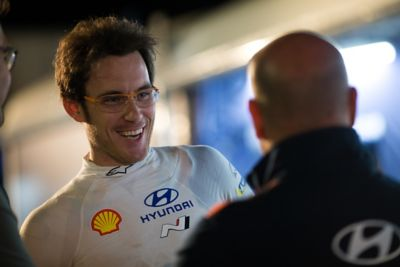 Hyundai Motorsport driver Thierry Neuville smiling in conversation with a team member