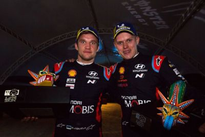 Hyundai Motorsport driver Ott Tänak and co-driver Martin Järveoja holding trophies in an evening shot