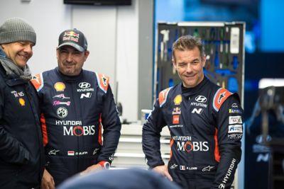 Kierowca i pilot Hyundai Motorsport Sébastien Loeb i Daniel Elena rozmawiający z członkiem ekipy