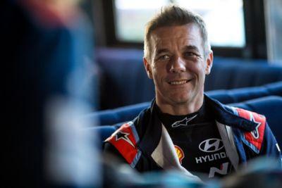 Kierowca Hyundai Motorsport Sébastien Loeb uśmiechający się do kogoś za kamerą