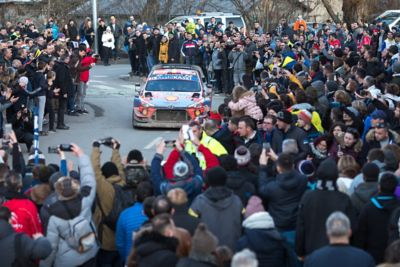 Hyundai Motorsport i20 Coupe WRC driving down a narrow road surrounded by a cheering crowd