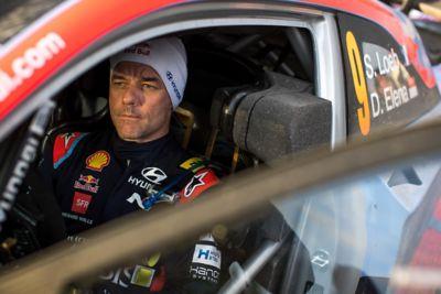Kierowca Hyundai Motorsport noszący czapkę Hyundai typu beanie siedzący przy otwartym oknie w samochodzie.
