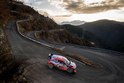 Hyundai i20 Coupe WRC jadący w dół wzgórza, zbliżający się do zakrętu w kształcie szpilki do włosów