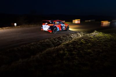 Hyundai Motorsport customer racing rally car i20 R5 in action at night with headlights on.