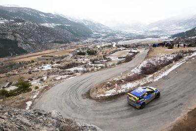 Hyundai Motorsport customer racing rally car i20 R5 in action driving a hairpin turn in the mountains.