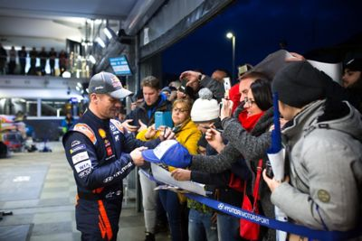 Hyundai Motorsport driver Sébastien Loeb signing autographs for fans on various items