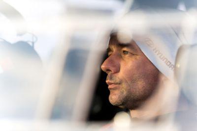 Close-up shot of Hyundai Motorsport driver Sébastien Loeb wearing a Hyundai beanie hat