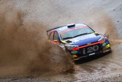 Hyundai Motorsport customer racing rally car i20 R5 splashing water on both sides.
