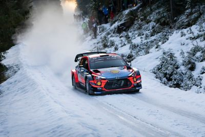 Hyundai Motorsport car driving in the snow with a spray-back of snow