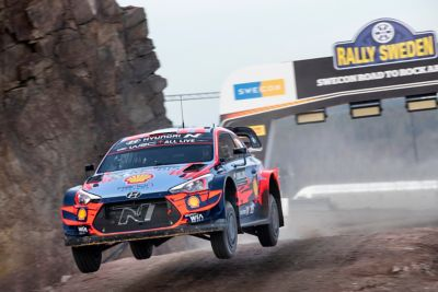 Hyundai i20 Coupe WRC speeding off the ground in the Rally Sweden
