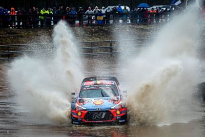 Hyundai i20 Coupe WRC driving  through a body of water with sprays of water extending to the side and behind