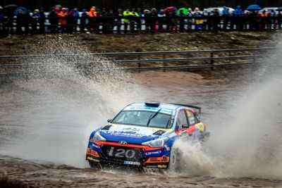 Hyundai Motorsport rally car i20 R5 driving through big puddle spraying water out 4 metres.