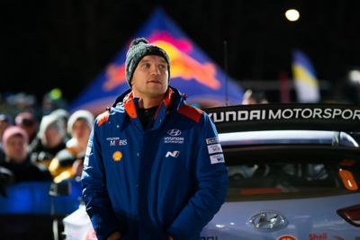 Hyundai Motorsport co-driver Martin Järveoja standing at the rear of the car in an evening shot