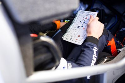 Hyundai Motorsport driver's hand holding a book