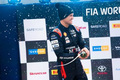 Hyundai Motorsport co-driver Martin Järveoja smiling whilst spraying champagne in celebration