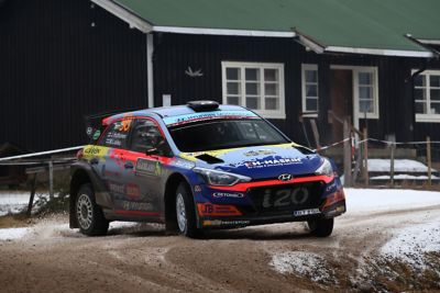 Hyundai Motorsport customer racing rally car i20 R5 in action on a snowy gravel road.