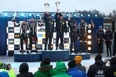 Hyundai Motorsport customer racing team shown on the podium after victory at Rally Sweden.