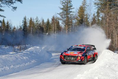 Hyundai Motorsport i20 Coupe WRC drifting around a bend leaving clouds of snow behind