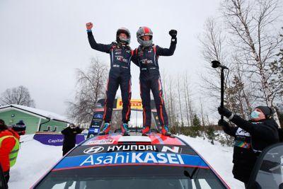 Hyundai Motorsport driver Ott Tänak and co-driver Martin Järveoja standing on the Hyundai i20 Coupe WRC, celebrating their win.