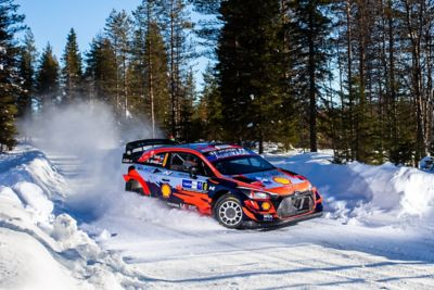 Hyundai i20 Coupe WRC driving through a mass of snow spraying both sides.