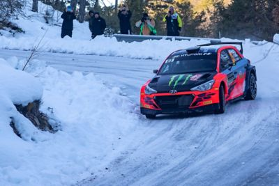 Hyundai Motorsport customer racing rally car i20 R5 in action on a snowy mountain road.