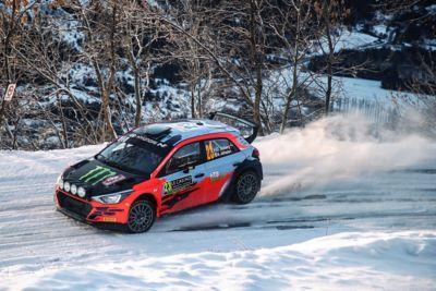 Hyundai Motorsport rally car i20 drifting through snow.
