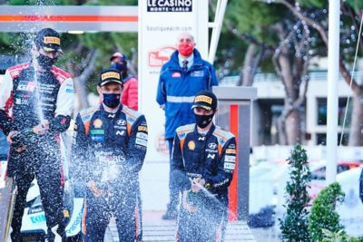 Hyundai Motorsport driver Thierry Neuville & co-driver Martijn Wydaeghe spraying champaign.