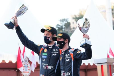 Hyundai Motorsport driver Thierry Neuville holding up their trophy.