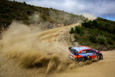 The Hyundai i20 Coupe WRC racing around a corner on a dirt road.
