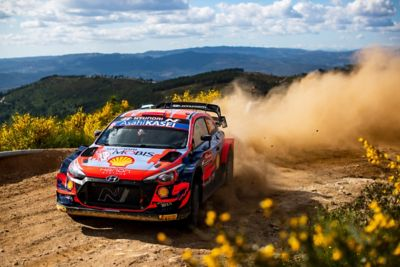 The Hyundai i20 Coupe WRC racing through a curve and throwing up dirt.